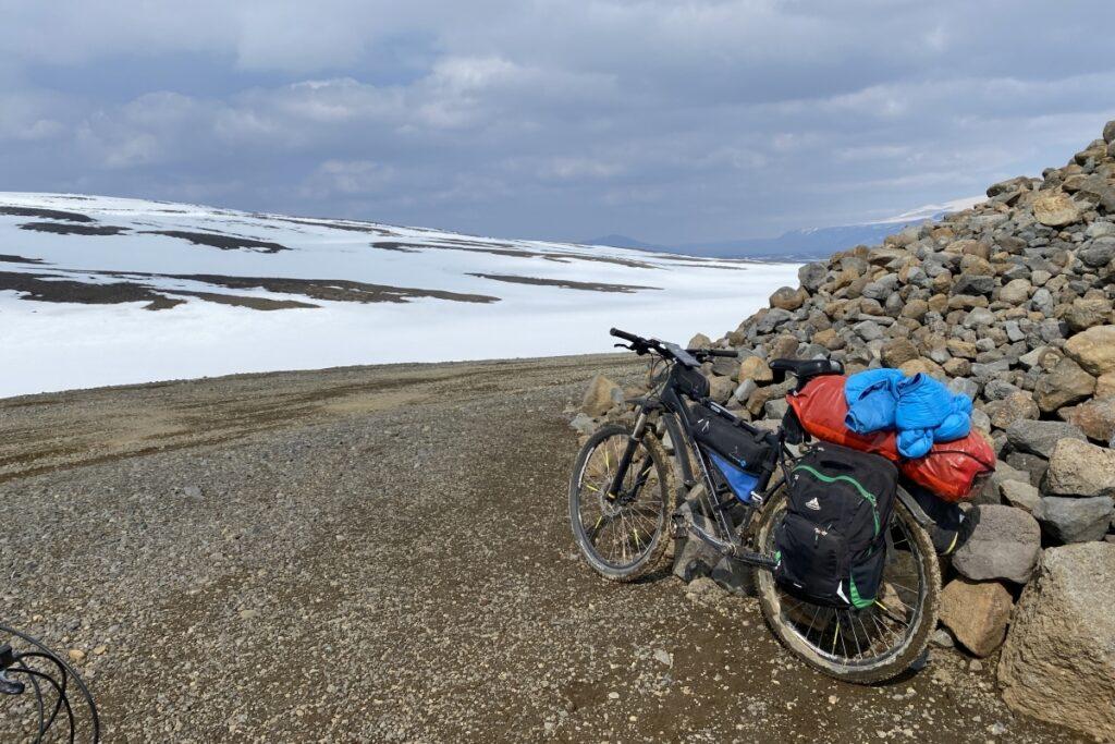 Ein Fahhrad ist an einem Steinhaufen angelehnt. Im Hintergrund sieht man einen schneebedeckten Hügel.