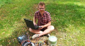 Benedikt Braszus sitzt auf der Wiese, hat einen Laptop auf dem Schoß und diverse Geräte vor sich liegen.