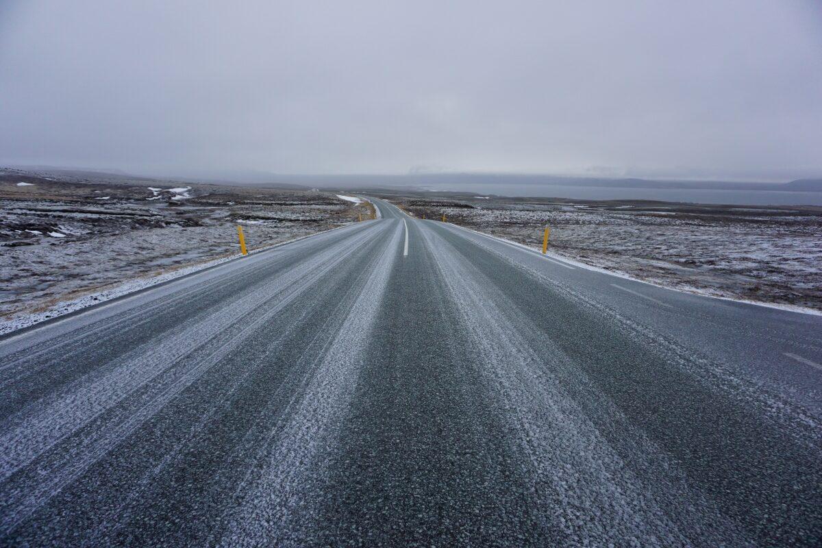 Eine leicht mit Schnee bedeckte Straße führt in Richtung Horizont und verschwindet im Nebel.