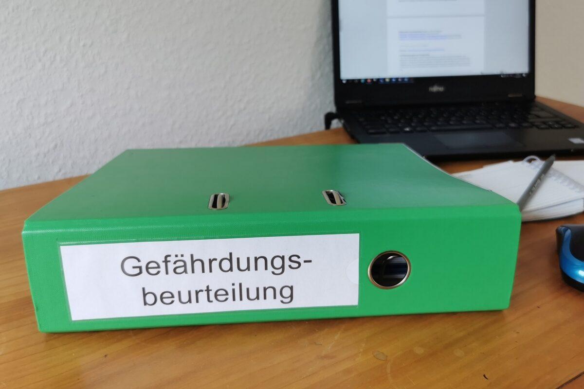 Ein gründer Ordner liegt auf einem Schreibtisch. Auf dem Ordner steht Gefährdungsbeurteilung. Im Hintergrund sieht man einen aufgeklappten Laptop. (Foto: Sara Burk, KIT)