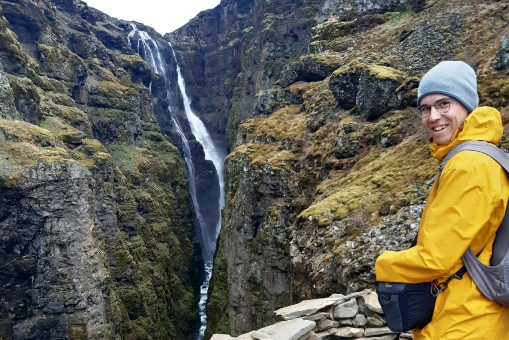 Andrej blickt in die Kamera. Hinter ihm ist eine schmale Schlucht zu erkennen. Am Ende der Schlucht ist ein hoher Wasserfall.