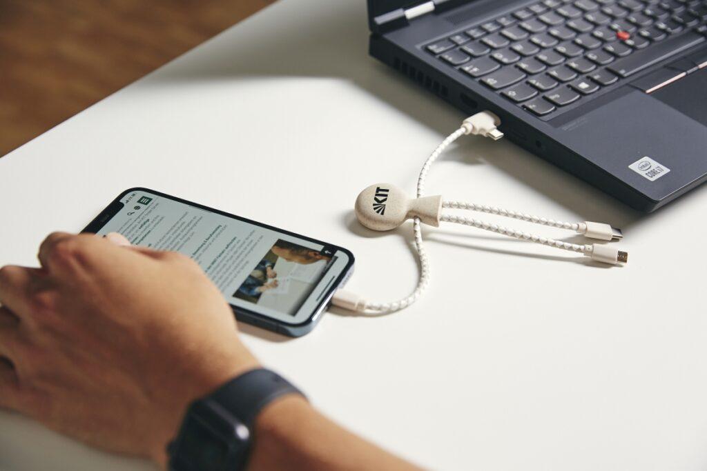 Ein Mobiltelefon liegt auf einem Tisch. Es ist durch ein Ladekabel mit einem aufgeklappten Laptop verbunden.