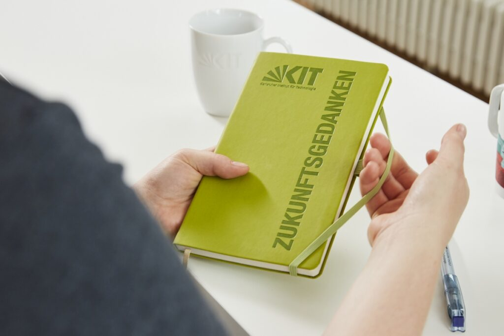 """Eine Person, von der man nur die Hände sieht, hält ein hellgrünes Notizbuch mit der Aufschrift """"Zukunftsgedanken"""" in der Hand. Auf dem Notizbuch ist auch das Logo des KIT zu sehen."""