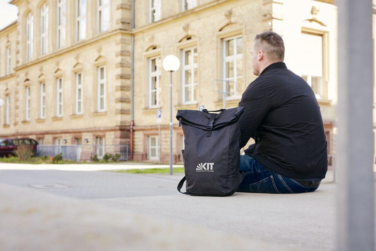 Eine Person, die man nur von hinten sieht, sitzt auf den Treppenstufen vor einem Gebäude. Neben ihr steht ein Rucksack mit dem KIT-Logo.