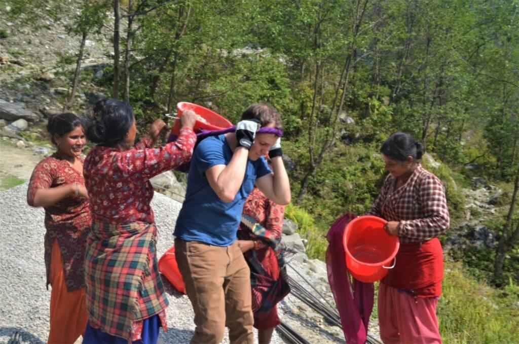 Ein Mann transportiert einen mit Geröll gefüllten Eimer, der mit einem Band an der Stirn befestigt ist. Eine Frau hilft ihm, den Eimer richtig am Rücken zu platzieren. Beide stehen zusammen mit anderen Menschen an einem Abhang.