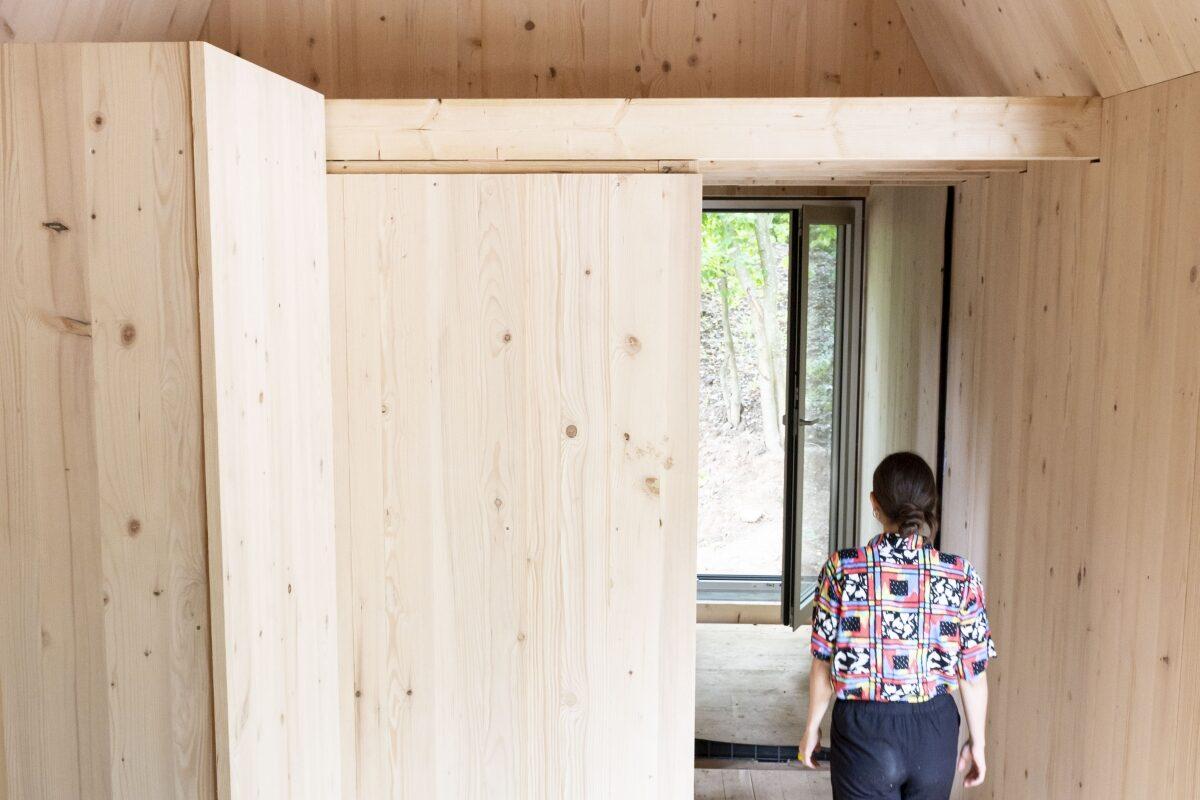 Innenansicht des Tiny Houses am Campingplatz Durlach. Die Wände sind holzverkleidet. Durch einen schmalen Durchgang läuft eine Frau.