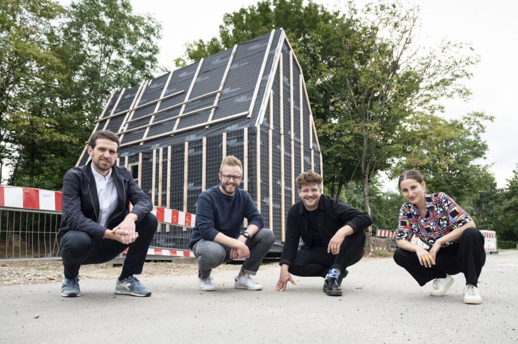 Im Vordergrund knien Peter Hoffmann, Adrian Obermüller, David Urich und Merve Şimşek und schauen in die Kamera. Im Hintergrund sieht man den Rohbau des Tiny House.