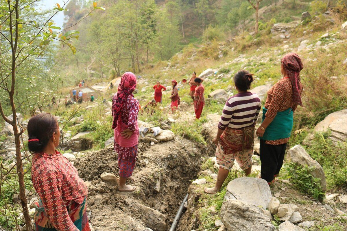 Eine Gruppe von Menschen steht an einem Berghang. Zwischen ihnen ist ein Graben ausgehoben, indem Wasserleitungen liegen.