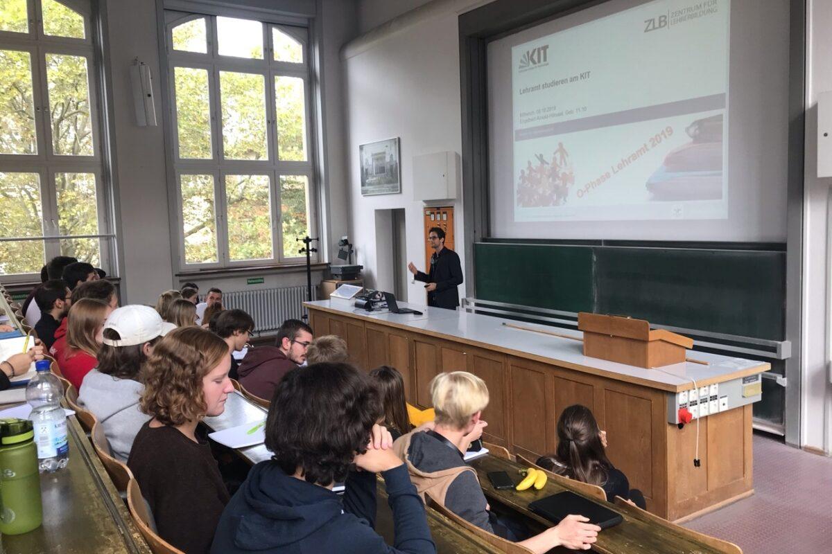"""Studierende sitzen in einem Hörsaal. Am Pult im hinteren Teil des Bildes hält ein Mann einen Vortrag. Auf der Folie eine Power-Point-Präsentation steht """"Lehramt studieren am KIT""""."""