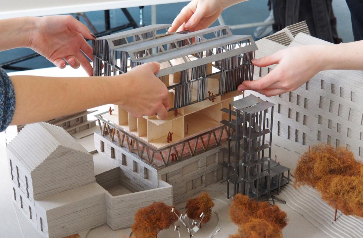 Ein Modell des Bauentwurfs von roofKIT wird von zwei Personen zusammengesetzt. Von beiden Personen sieht man nur die Hände.