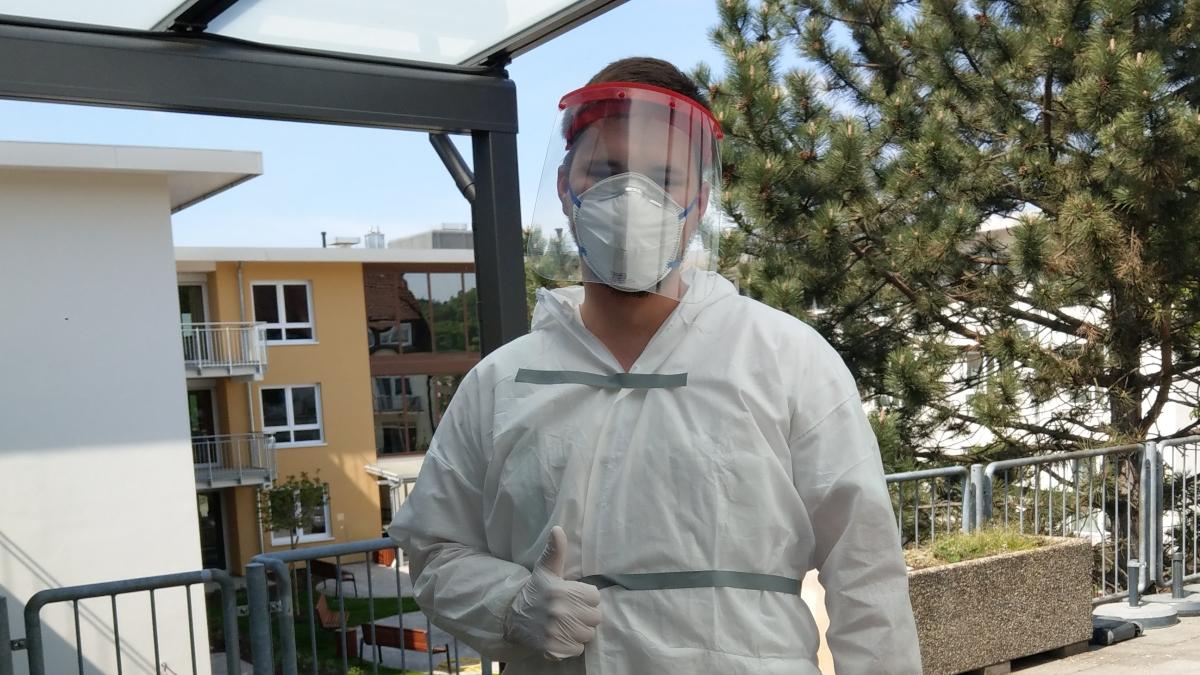 Valentin Mattis steht im Schutzanzug mit FFP2-Maske und Schutzvisier auf der Terasse des Seniorenheims und schaut in die Kamera.
