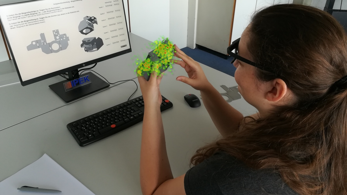 Eine Studentin sitzt am Schreibtisch vor Ihrem Computer und überprüft das von ihr konstruierte Bauteil.