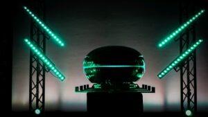 """Bild von der Präsentation des Prototypen """"Neowise"""". Der schwarze Pod wird von grünen Lichtern angeschienen."""